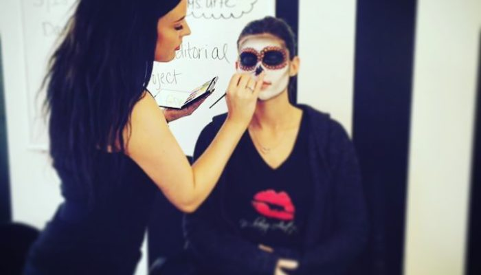 Applying sugar skull makeup during halloween.