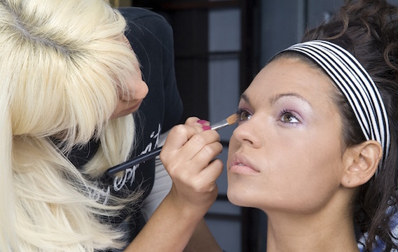 A cosmetologist applying makeup to a model's eyes.