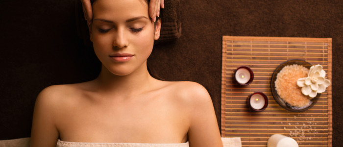 Woman in a towel getting a head massage in a spa.
